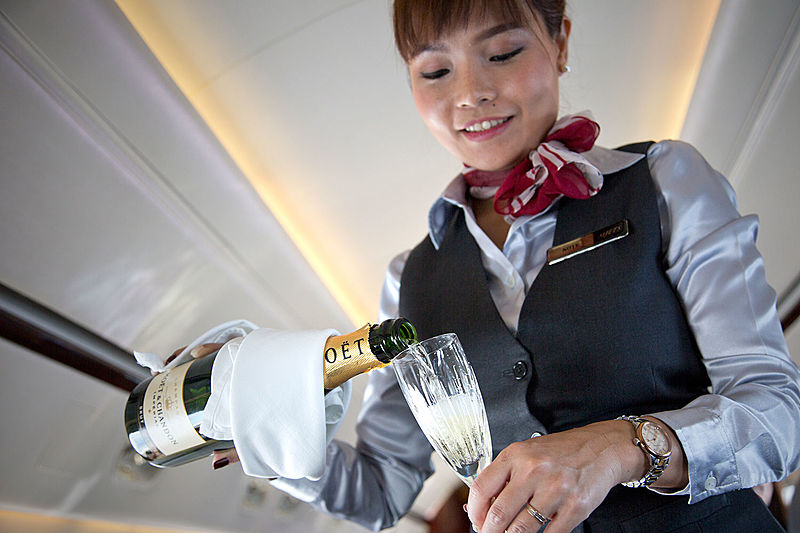 MJets stewardess pouring champagne