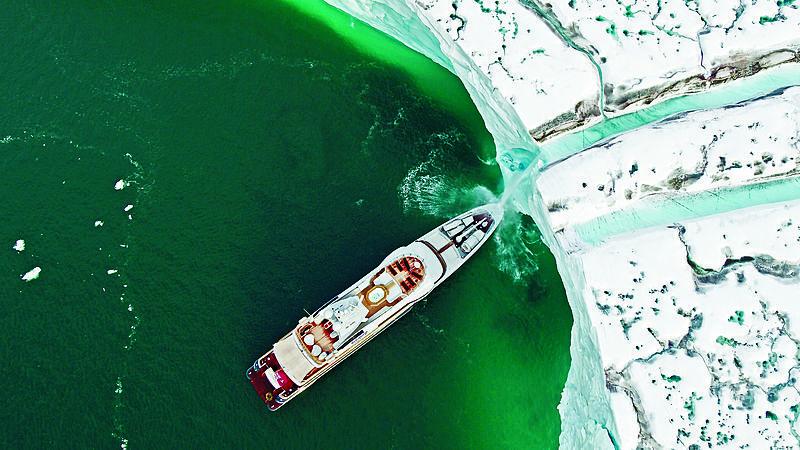Gene Machine yacht in front of a glacier